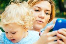 Mama używa telefonu podczas zabawy z dzieckiem